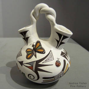 Butterfly, lady bug and geometric designs on a polychrome wedding vase with a twisted handle