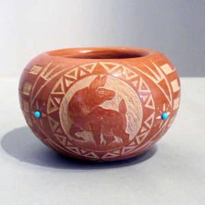 Sgraffito animal and geometric design on a red bowl with inlaid turquoise accents