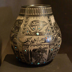 A mix of Sioux and Santa Clara sgraffito designs plus inlaid turquoise decorate a polished black jar