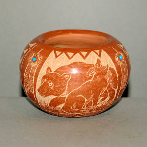 Sgraffito bear, wolf and Sioux design on a red jar with inlaid stones