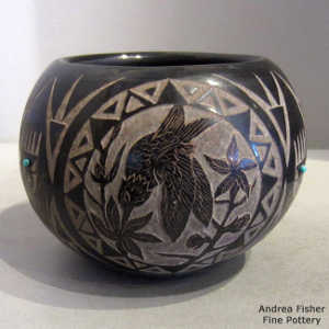 Sgarffito animal and geometric design on a black jar with inlaid stones