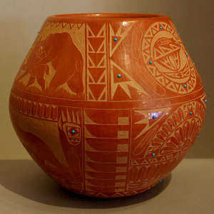 Sgraffito Sioux design plus inlaid stones on a red jar