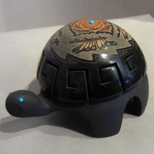 Sgraffito butterfly, flower and geometric designs on a carved black turtle with inlaid turquoise