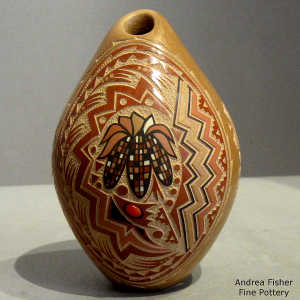A sgraffito and painte3d ears of corn and geometric design on a polychrome seed pot with an inlaid garnet