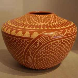 Geometric sgraffito designs on a red jar