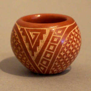 Sgraffito geometric design on a miniature red bowl