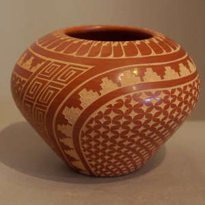 Sgraffito geometric design on a polished red jar