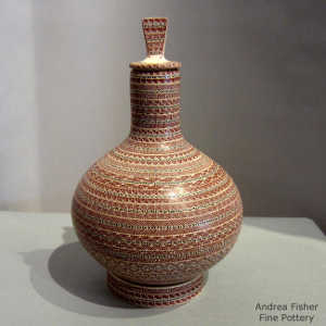 Bands of geometric design on a lidded polychrome jar with a matching stand