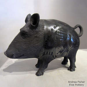 Carved head and legs and Paquime designs on the body of a black on black javelina