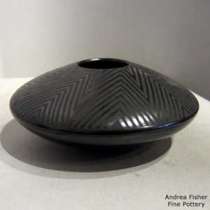 Geometric design on a black on black flying saucer jar