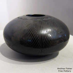 Fine line and geometric design on a black on black jar