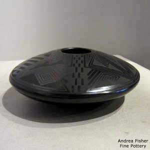 Shard geometric design on a black on black flying saucer jar