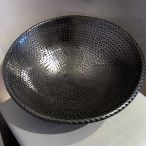 Textured surface in side and out on a large polished black bowl