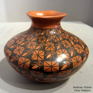 Ant and geometric designs decorate a red and black jar with a square opening