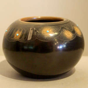 Sgraffito feather and avanyu design on a black jar with sienna spots and inlaid stones