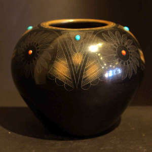 Sgraffito medallion and geometric design on a polished black jar with sienna spots and inlaid coral and turquoise