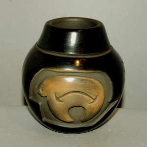 Bear and geometric design carved into a black jar with a sienna spot