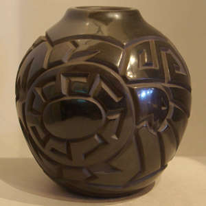 Bird and geometric designs carved into a polished black jar