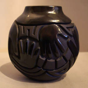 Hands and geometric design carved into a polished black jar