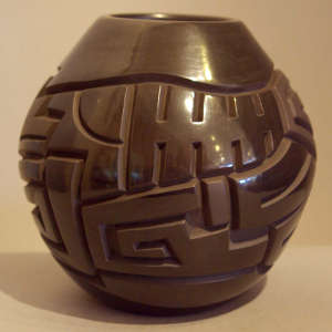 Geometric design carved into a polished black jar