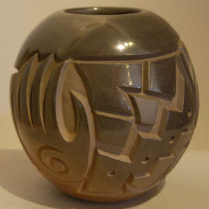 Hand, bear, kiva step and geometric design carved into a polished brown jar