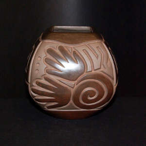 Hand, spiral and geometric design carved into a brown on brown jar