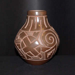 Spiral, turtle and geometric design carved into a brown on brown jar