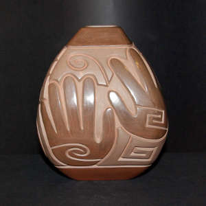 Spiral, hand and geometric design carved into a brown on brown jar with a square opening