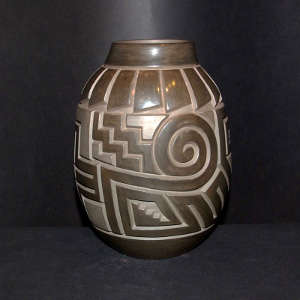Feathers, bear paw, spiral and cross design carved in a brown on brown jar