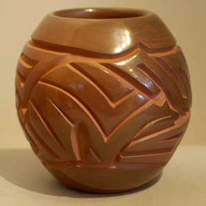 Stylized bear and geometric design carved into a brown jar