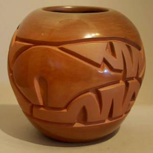 Bear and stylized heart line design carved into a brown jar