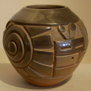 Spiral, katsina faces and geometric design carved into a black jar