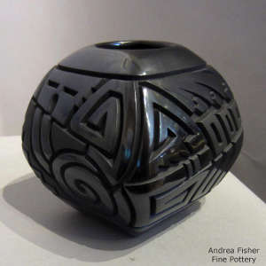 Geometric design carved into a square black on black jar
