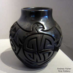 Stylized eagle and geometric design carved into a black on black jar