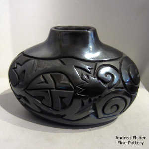 Spiral, rabbit, horned toad and geometric design carved into a black on black oval jar