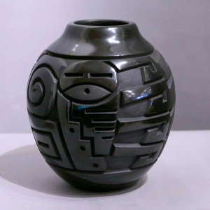 Kachina and geometric design carved into a black jar
