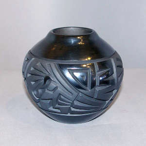 Kokopelli and geometric design carved into a black on black jar