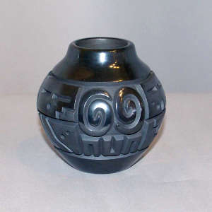 Spiral, sun face and geometric design carved into a black on black jar