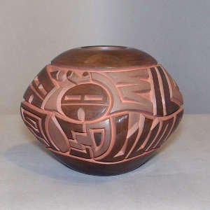 Sun face and geometric design carved into a squarish polished and matte brown jar