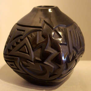 Lizard and geometric design carved into a squarish black on black jar