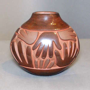 Spiral, hand and geometric design carved into a brown oblong jar