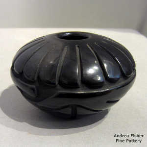 Feather and geometric design carved into a polished black jar