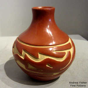 An avanyu design carved into a polished red jar