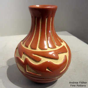 Avanyu and geometric design carved into a polished red jar