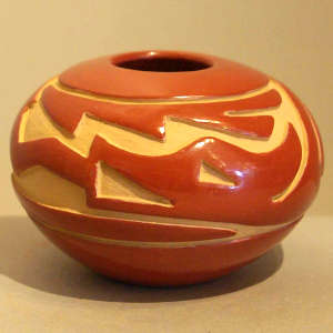 Avanyu design carved into a red jar