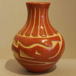 Feather and avanyu design carved into a polished red jar