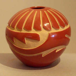 Feather and geometric design carved into a polished red jar