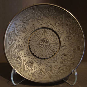 Feather and geometric designs carved into a black plate