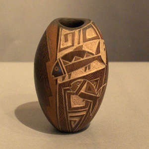 Sgraffito fish and geometric design on a brown jar with an oval opening