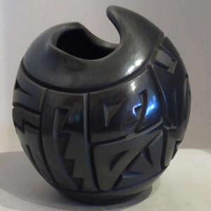 Black jar with organic opening carved with geometric design